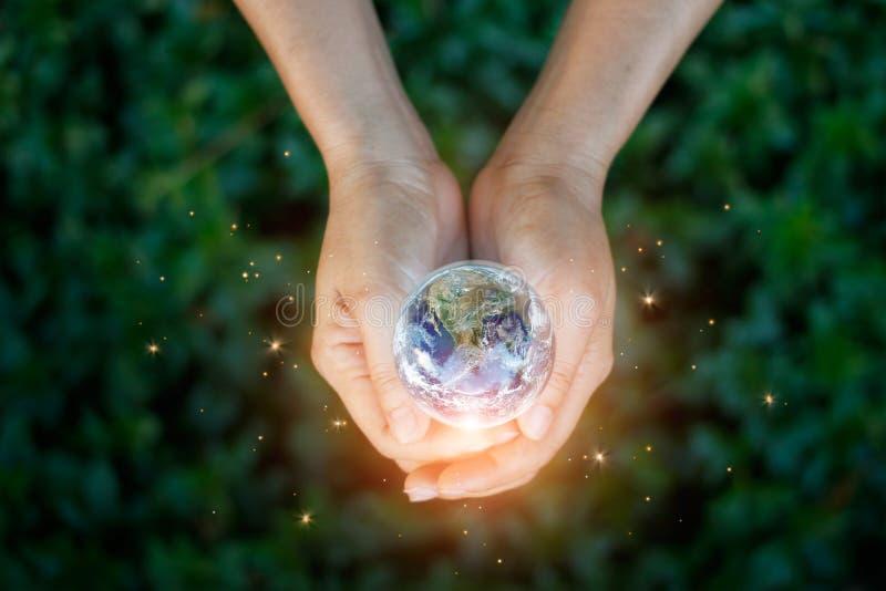 Het concept van de besparingsenergie, de aarde van de Handholding tegen aard stock afbeelding