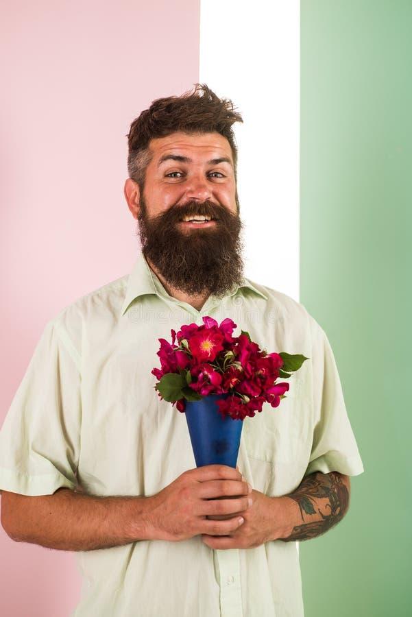 Het concept van de bloemenlevering De mens met baard vrolijk gezicht houdt boeket verse bloemen De kerel houdt boeket zeker ongev stock afbeelding