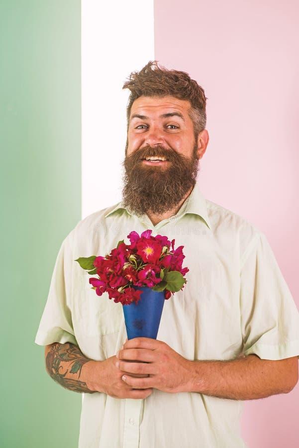 Het concept van de bloemenlevering De mens met baard vrolijk gezicht houdt boeket verse bloemen De kerel houdt boeket zeker ongev royalty-vrije stock fotografie