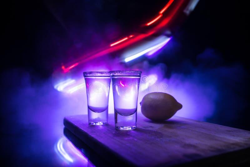 Het concept van de clubdrank De smakelijke alcohol drinkt cocktailtequila met kalk en zout op trillende donkere achtergrond of gl stock foto