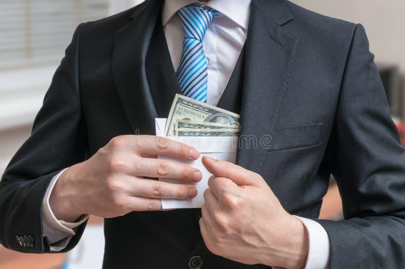 Het concept van de corruptie De zakenman verbergt brievenhoogtepunt van geld of steekpenning in kostuumjasje stock foto's