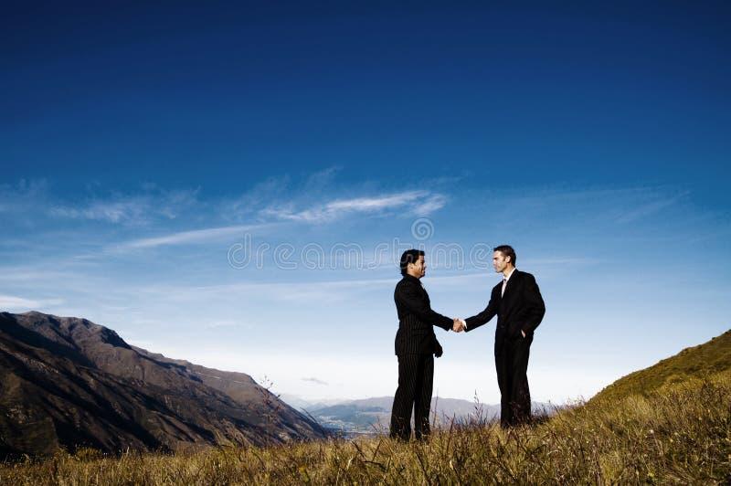 Het Concept van de de Bergketenvoltooiing van de zakenliedenhanddruk stock fotografie