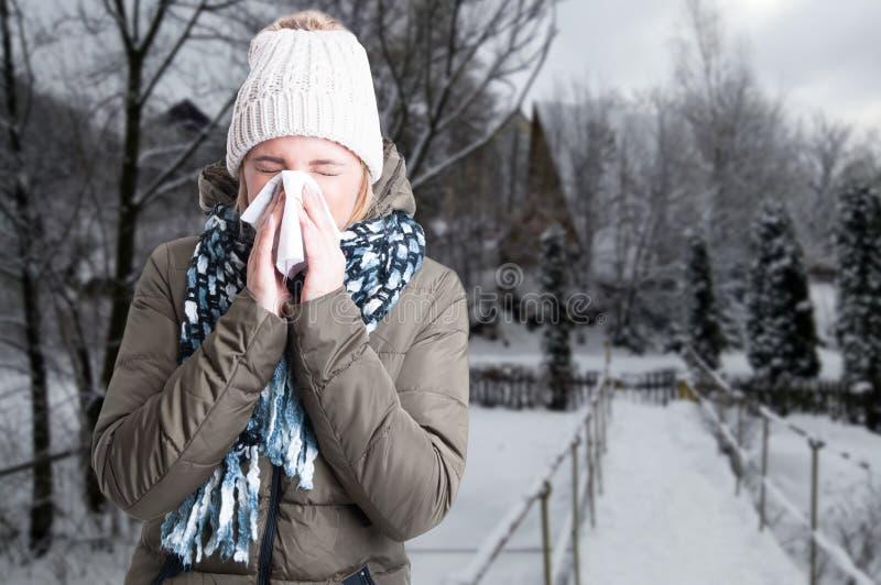 Het concept van de de winterziekte met vrouw het blazen in servet stock foto