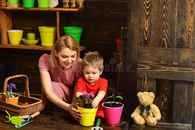 Het concept van de ecologie Weinig moeder die van de zoonshulp bloem planten aan nieuwe pot, ecologie Ecologie en milieu Installa royalty-vrije stock afbeeldingen
