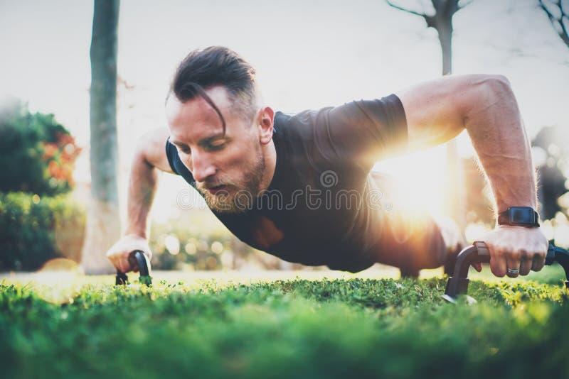 Het concept van de geschiktheidslevensstijl Spieratleet die duw op buitenkant in zonnig park uitoefenen Geschikt shirtless mannel stock fotografie