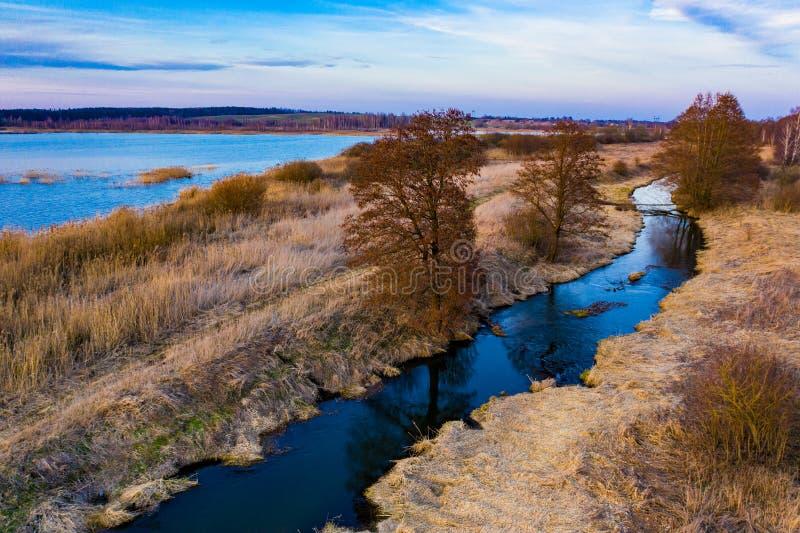 Het concept van de herfst Ge?soleerd Droge die gras en bomen door blauw meer en smalle rivier, luchtlandschap wordt omringd stock fotografie