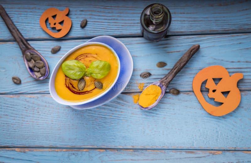 Het concept van het de herfstmenu De soep van de pompoenroom met pompoenzaden, pompoenolie en kurkuma op een blauwe achtergrond H stock fotografie