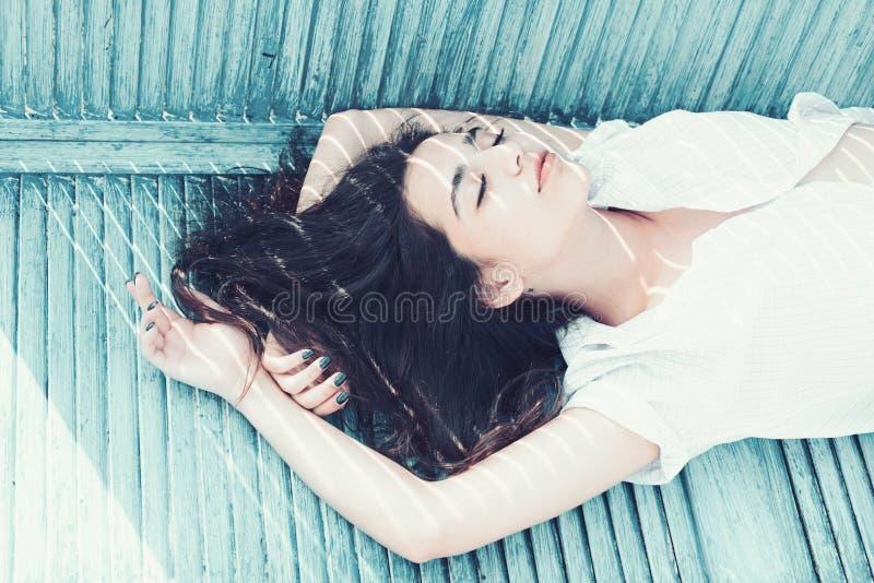 Het concept van de hitte Vrouwenbrunette die terwijl tribunes dichtbij jaloezie koelen, strepen van zonlicht en schaduw op haar g stock fotografie