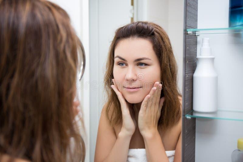 Het concept van de huidzorg - gelukkige vrouw die spiegel bekijken stock foto