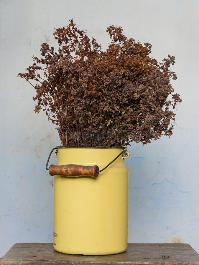 Het concept van de huisdecoratie: droge weidebloemen in een gele metaalpot op oude houten kruk met spijkers die uit plakken royalty-vrije stock afbeeldingen