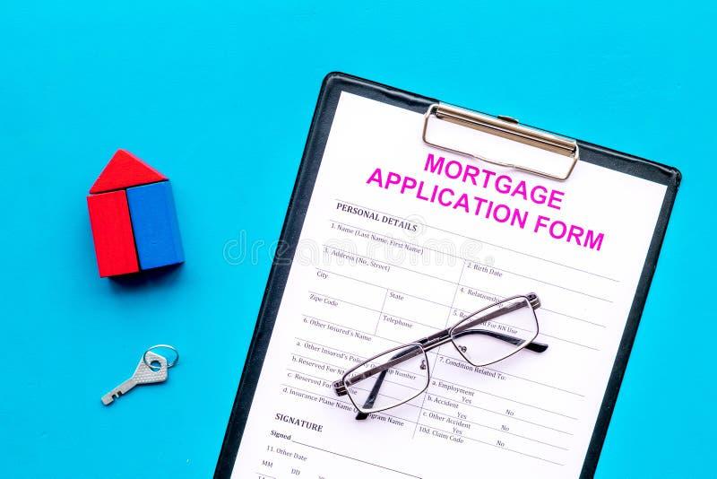 Het concept van de hypotheek Hypotheekaanvraagformulier dichtbij sleutel en huis van aannemer op blauwe hoogste mening wordt gema stock foto's