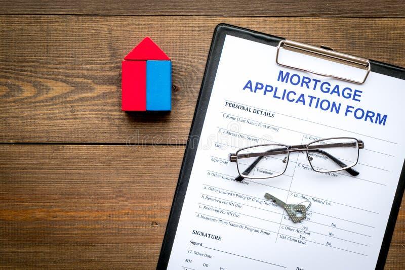 Het concept van de hypotheek Hypotheekaanvraagformulier dichtbij sleutel en huis van aannemer op donkere houten hoogste mening wo stock fotografie