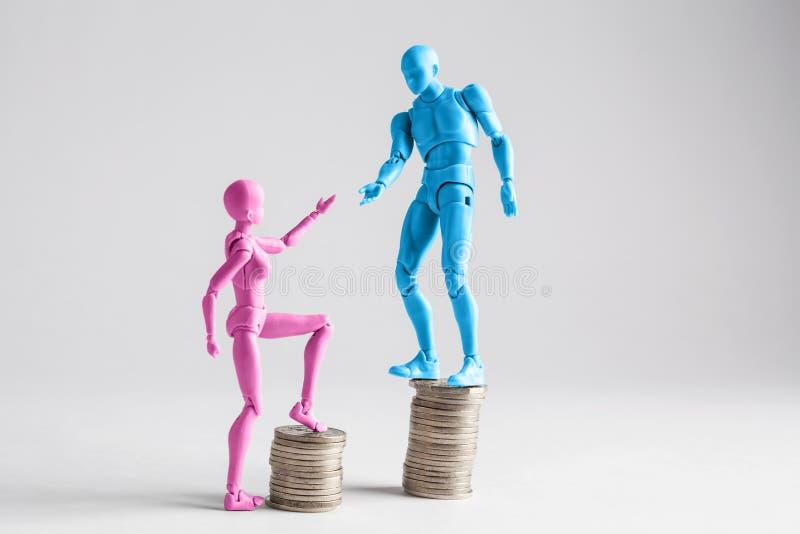 Het concept van de inkomensongelijkheid met realistische mannelijke en vrouwelijke beeldjes en stapels van muntstukken wordt geto stock foto's