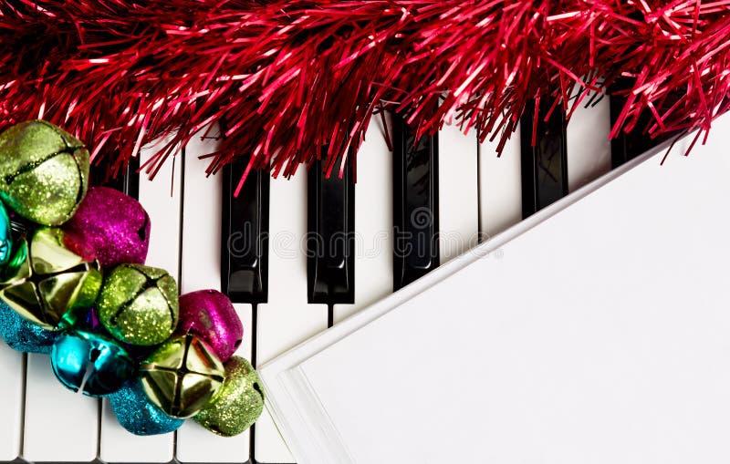 Het concept van de Kerstmismuziek Leeg document op de piano met kenwijsjeklokken en rood klatergoud royalty-vrije stock foto