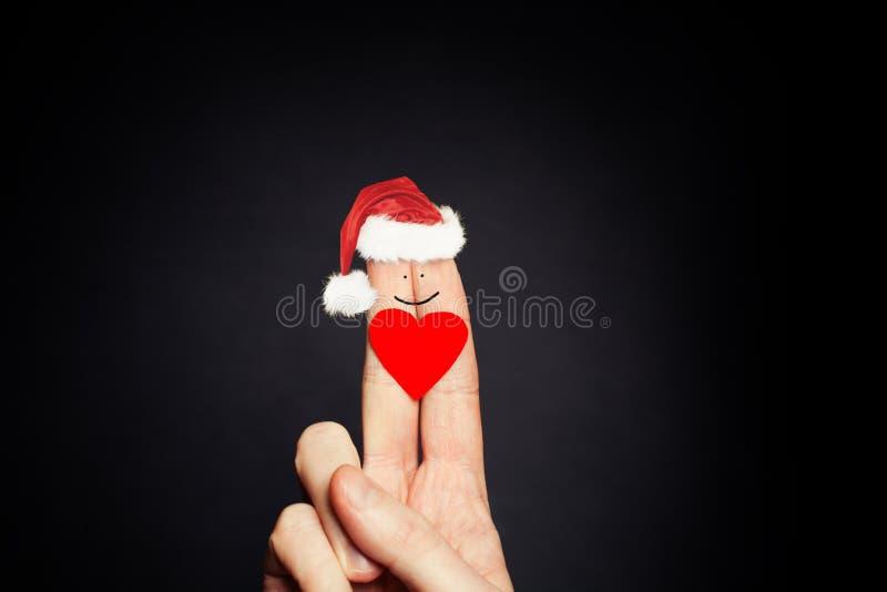 Het concept van de Kerstmisvakantie Gelukkig vingersgezicht in Santa Hats Paarverhoudingen royalty-vrije stock afbeelding