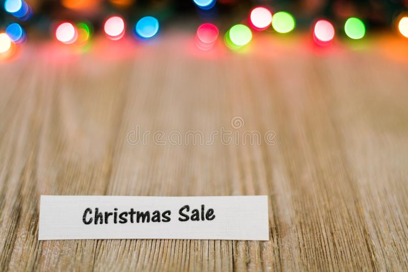 Het Concept van de Kerstmisverkoop op houten raad en gekleurde lichten, selectieve nadruk, ruimte voor exemplaar stock foto