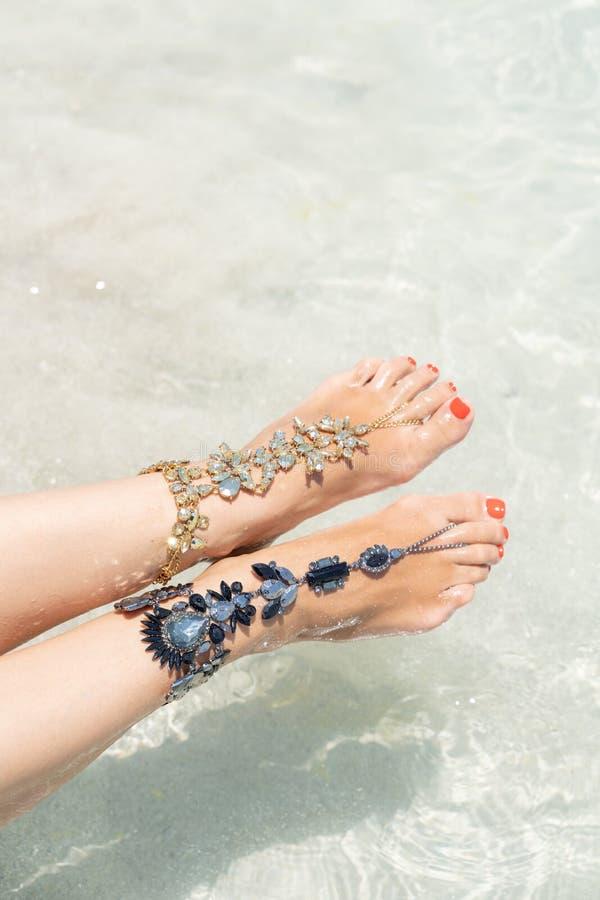 Het concept van de kuikenvakantie vibe Vrouwenbenen met beenjuwelen op het tropische witte zandstrand royalty-vrije stock foto's