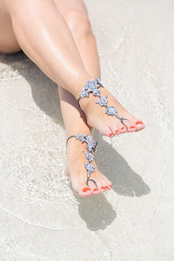 Het concept van de kuikenvakantie vibe Vrouwenbenen met beenjuwelen op het tropische witte zandstrand stock fotografie