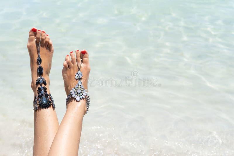 Het concept van de kuikenvakantie vibe Vrouwenbenen met beenjuwelen op het tropische witte zandstrand stock foto