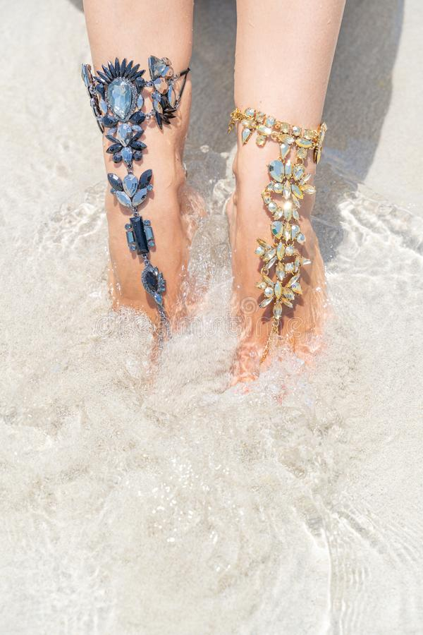 Het concept van de kuikenvakantie vibe Vrouwenbenen met beenjuwelen op het tropische witte zandstrand stock afbeeldingen