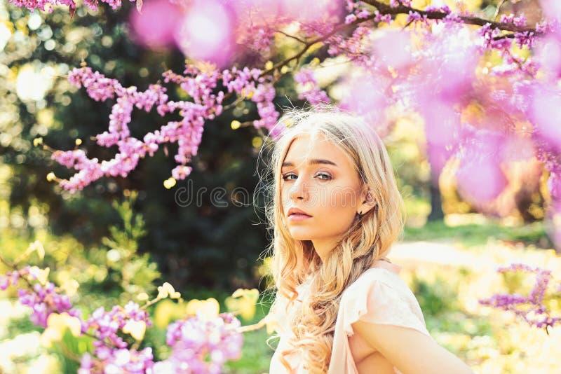 Het concept van de de lentebloei Meisje op dromerig gezicht, teder blonde dichtbij violette bloemen van judasboom, aardachtergron royalty-vrije stock foto's