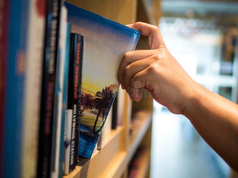 Het concept van de lezing het mannelijke hand kiezen en het plukken boek in een boekenrek Boekreisverhaal, onderwijsonderzoek en  stock foto's