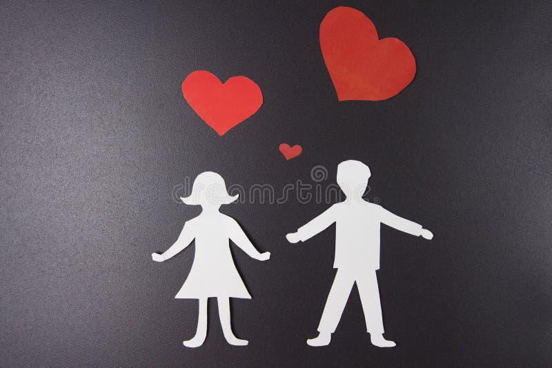 Het concept van de liefde Document rode harten over de mens en vrouw in liefde op zwarte achtergrond St de Dag van de valentijnsk stock foto