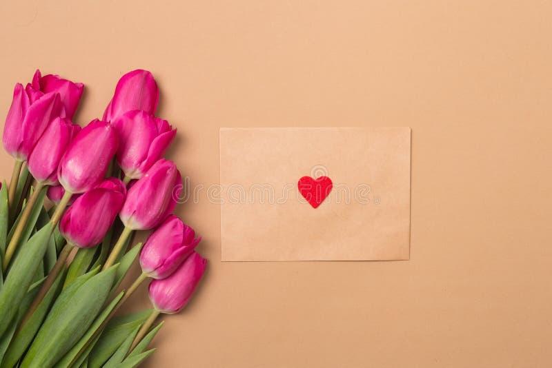 Het concept van de liefde De stemming van de lente Bloeien de de lente beige achtergrond met de lenteroze en de ambachtenvelop me royalty-vrije stock foto's