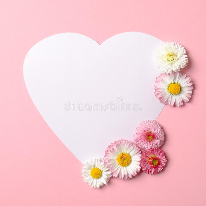 Het Concept van de liefdeaard Daisy bloemen en witte hart-vormige document kaart op pastelkleur roze achtergrond vlak leg samenst stock foto's