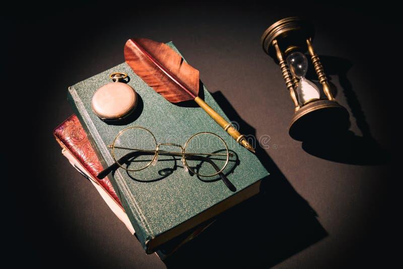 Het concept van de literatuur Uitstekend stilleven met zandloper dichtbij glazen op oude boeken dichtbij veer of schacht en klok stock foto's