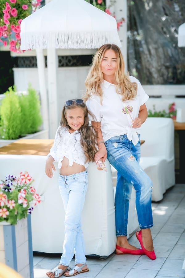 Het concept van de manierfamilie - modieuze moeder en kindslijtage Een portret van een gelukkige familie: een jonge mooie vrouw m stock fotografie