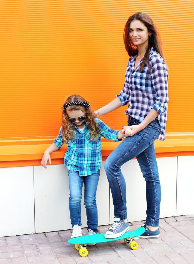 Het concept van de manierfamilie - moeder en kind die op skateboard berijden stock fotografie