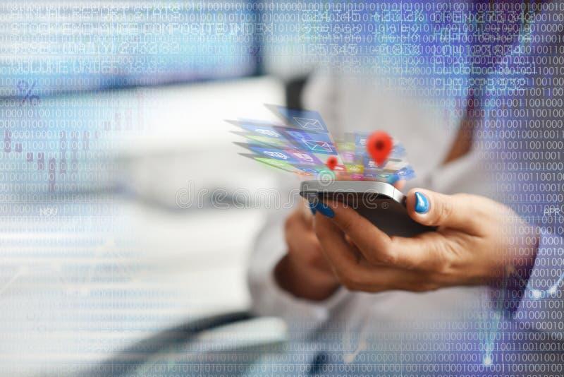 Het concept van de mobiele toepassingontwikkeling met vrouwelijke ontwikkelaar die smartphone met toepassingen hierboven pictogra stock foto