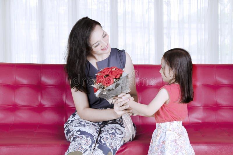 Het concept van de moeder` s dag: De dochter geeft een boeket van rode rozen aan moeder royalty-vrije stock foto