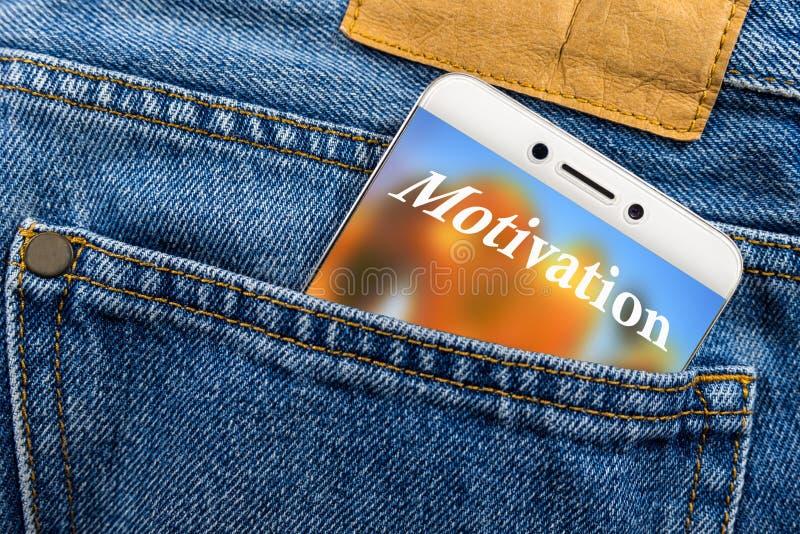 Het concept van de motivatietekst op de vertoning van een smartphone in een jeanszak die wordt geplaatst stock foto