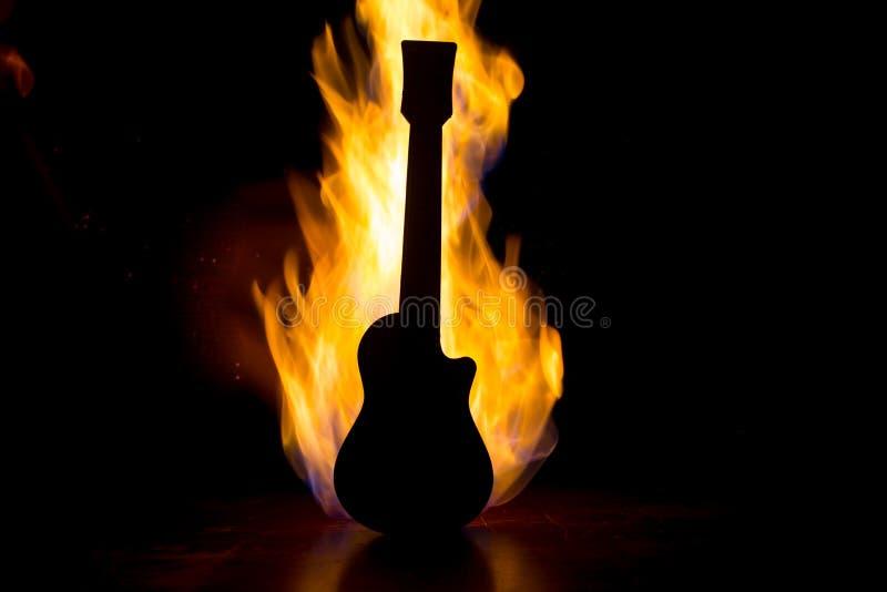 Het concept van de muziek Akoestische die gitaar op een donkere achtergrond onder lichtstraal met rook met exemplaarruimte wordt  royalty-vrije stock foto