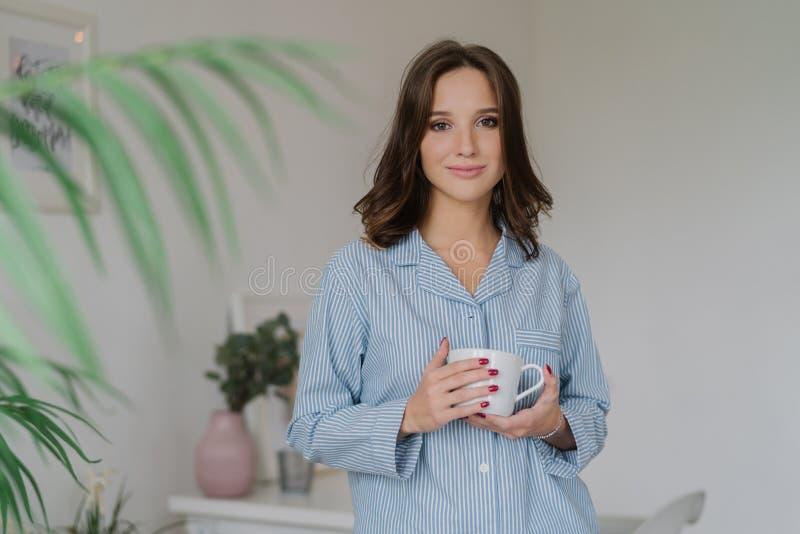 Het concept van de ochtendtijd De jonge vrij Europese vrouw in nightclothes draagt witte mok koffie of de cappuccino, bevindt zic royalty-vrije stock foto's