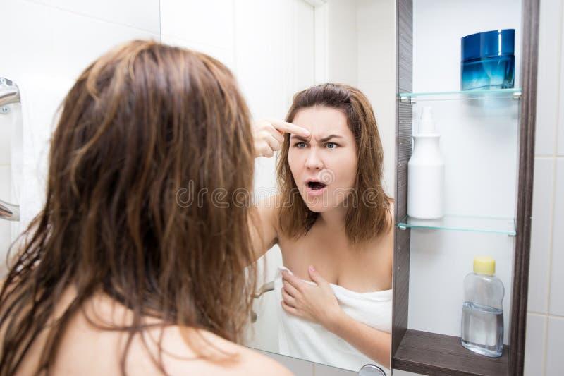 Het concept van de probleemhuid - verraste vrouw die spiegel in bad bekijken royalty-vrije stock fotografie