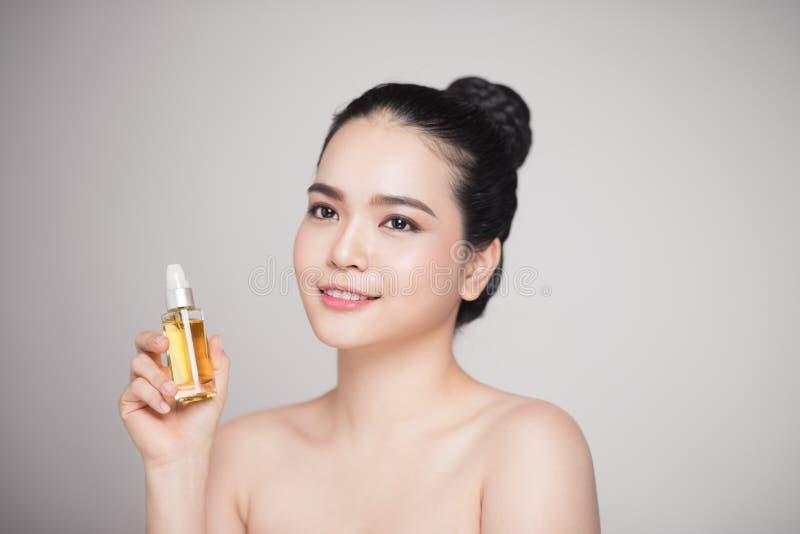Het concept van de schoonheid Aziatische mooie vrouw met de perfecte olie van de huidholding stock fotografie