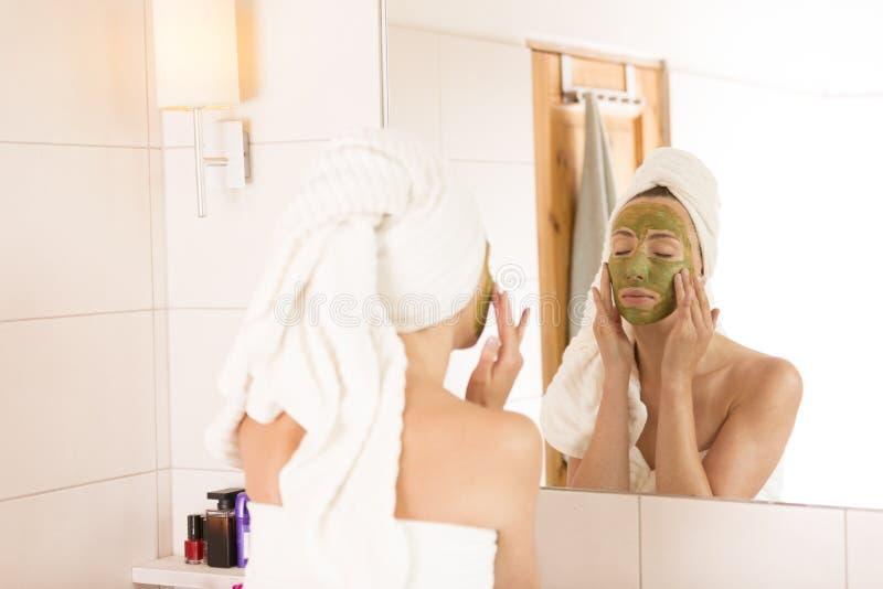 Het concept van de schoonheid De vrouw past groen organisch gezichtsmasker in de badkamers toe stock foto's