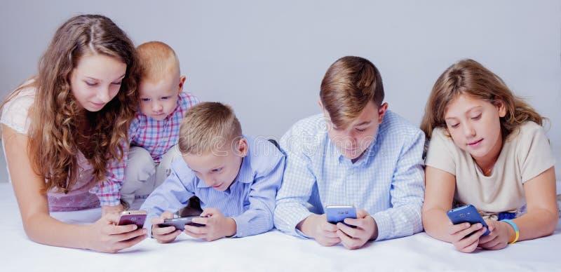 Het concept van de spelverslaving Groep die jonge geitjes elektronische apparaten met behulp van stock foto