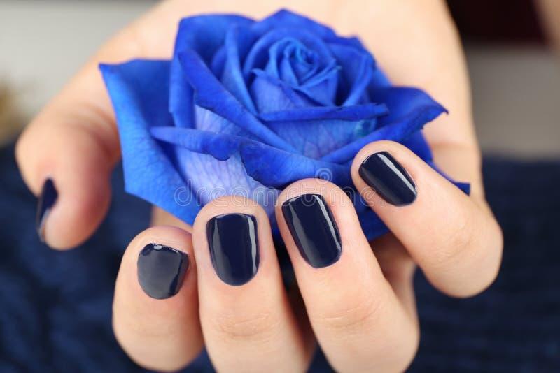 Het concept van de spijkerkunst De mooie vrouwelijke hand die blauw nam houden toe stock foto