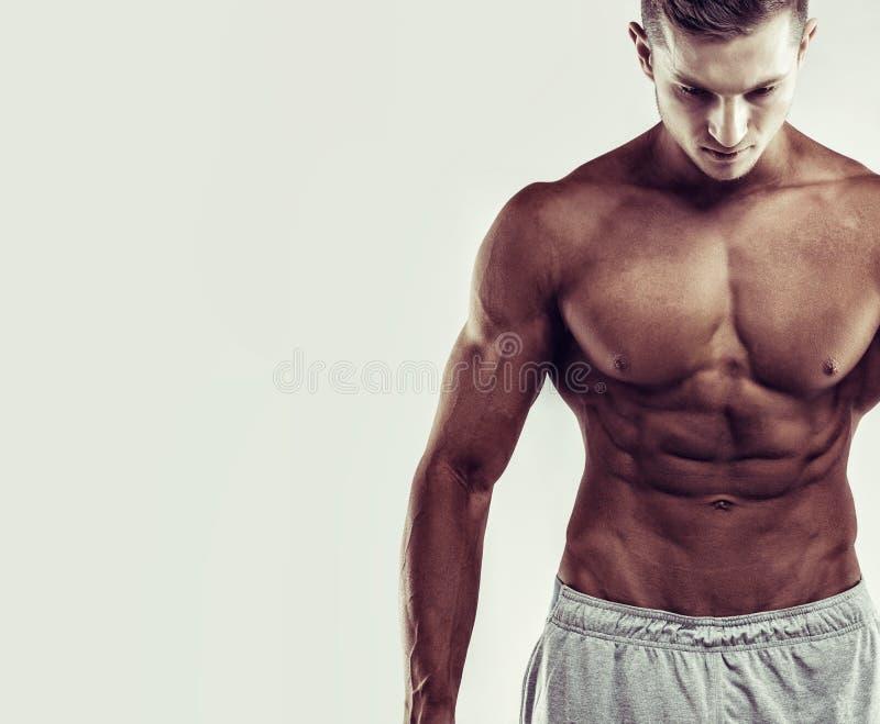 Het concept van de sport Sluit omhoog beeld van spier Kaukasisch mannetje in sporten die zich over grijze achtergrond kleden royalty-vrije stock afbeeldingen