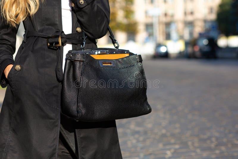 Het concept van de straatmanier Vrouw die in modieuze uitrusting zwart le houden royalty-vrije stock fotografie