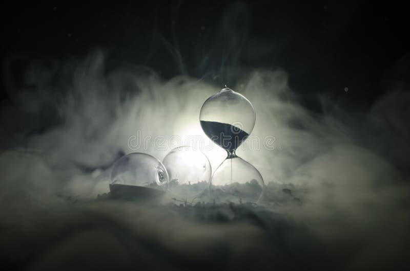 Het concept van de tijd Silhouet van Zandloperklok en rook op donkere achtergrond met hete geeloranje verlichting, of symbolen va stock foto's