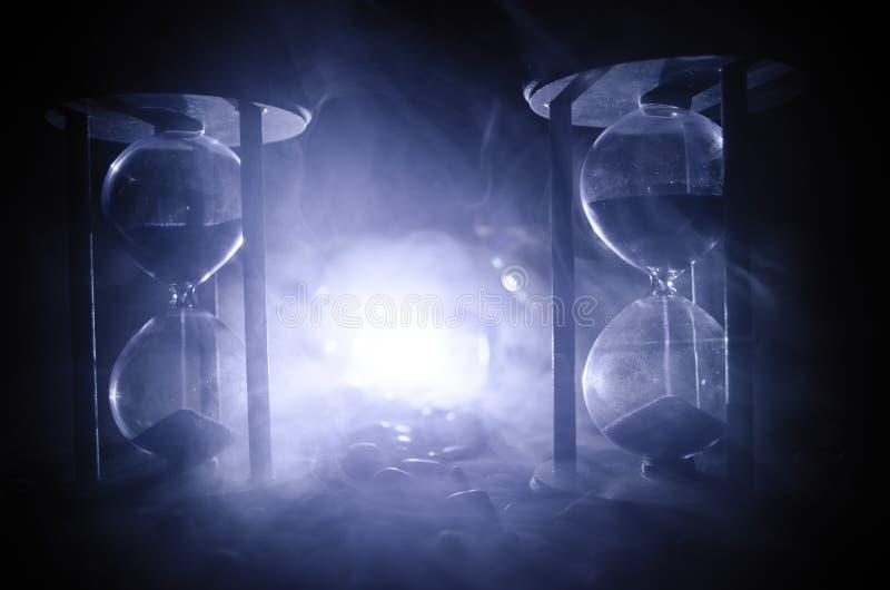 Het concept van de tijd Zand die door de glasbollen overgaan van een zandloper die de voorbijgaande tijd meten aangezien het neer stock afbeelding