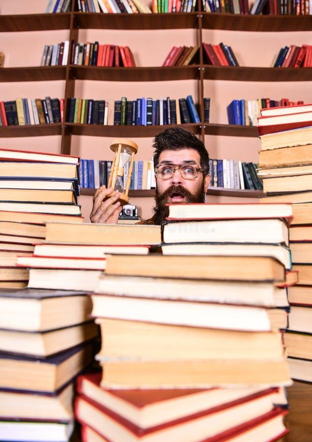 Het Concept van de tijdstroom De mens op verrast gezicht houdt zandloper terwijl het bestuderen, boekenrekken op achtergrond Lera royalty-vrije stock foto's