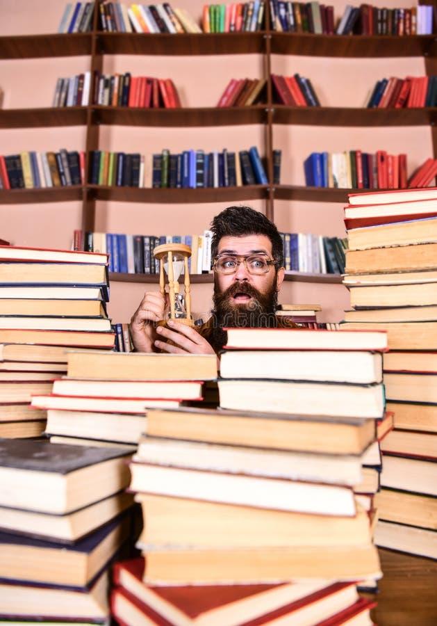 Het Concept van de tijdstroom De mens op verrast gezicht houdt zandloper terwijl het bestuderen, boekenrekken op achtergrond Mens royalty-vrije stock afbeeldingen