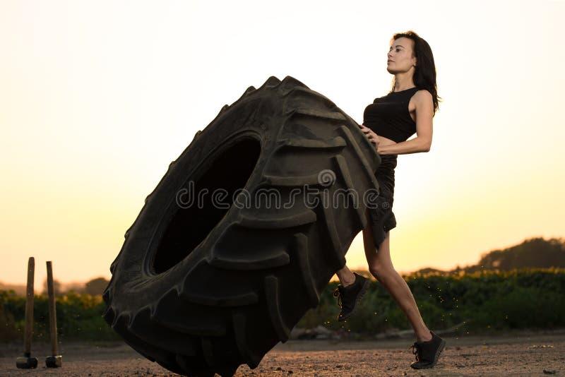 Het concept van de traininggeschiktheid De sportenvrouw keert bandwiel in gymnastiek, zweetdalingen, kracht om royalty-vrije stock afbeelding