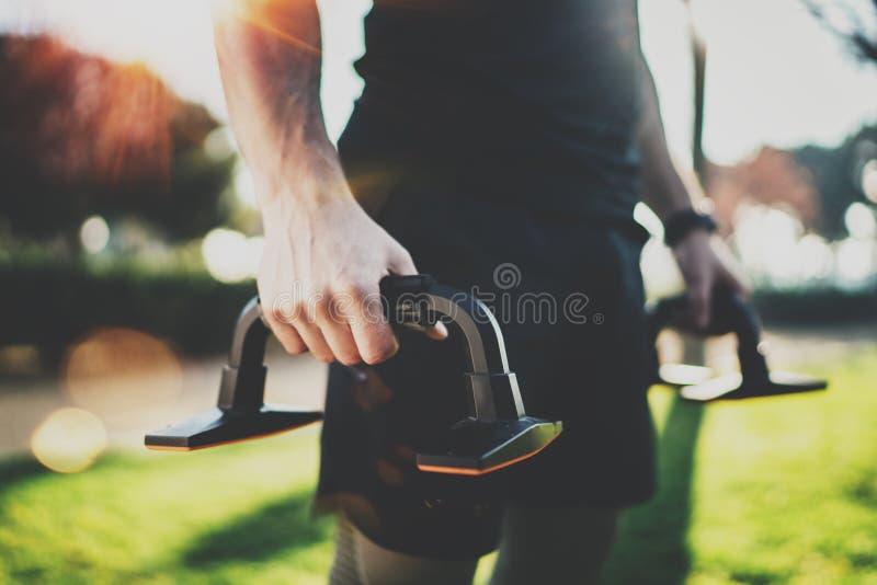 Het concept van de traininglevensstijl Close-upmening die van de Jonge mens zijn wapensspieren uitrekken vóór functionele openluc stock afbeelding